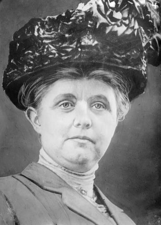 A black-and-white photograph of a woman wearing a large, decorative hat