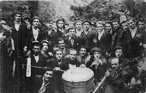 Rows of men in the woods holding musical instruments. They dress in Western or traditional styles.