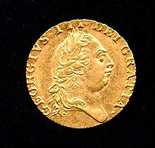 Gold coin bearing the profile of a round-headed George wearing a classical Roman-style haircut and laurel-wreath.