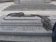 A granite tomb engraved with The Unknown Soldier on the side; a bronze relief sculpture is atop the sarcophagus