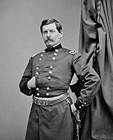 Man with mustache and military uniform, striking a Napoleon pose