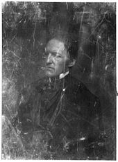 A scratched, half-length photographic portrait of a middle aged man in formal mid-19th century dress, facing left