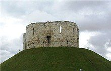 A photograph of a small castle on top of a green mound; the castle has three circular walls visible. Behind the castle the sky is overcast and dark grey.