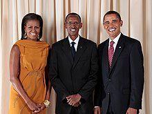 米歇尔·奥巴马、保罗·卡加梅与贝拉克·奥巴马一同站立于一块布帘前微笑合影。
