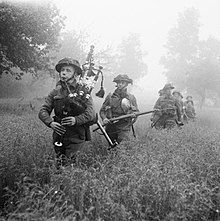 Bagpiper leading a line of soldiers though thigh-high growth