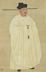 A man in heavy white robes, wearing a black hat with long horizontal protrusions coming from the bottom of the hat.
