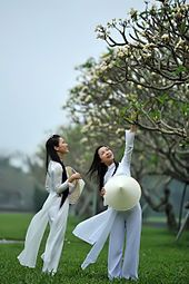 Photograph of two girls wearing a traditional Vietnamese white school uniform, the áo dài—both are holding the nón lá, a conical hat