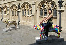 Tow pig statues in front of yellow stone building with arched windows. The nearest status is multi coloured band being ridden by person.