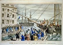 Two ships in a harbor, one in the distance. On board, men stripped to the waist and wearing feathers in their hair throw crates of tea overboard. A large crowd, mostly men, stands on the dock, waving hats and cheering. A few people wave their hats from windows in a nearby building