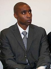 Soccer player Eddie Pope sitting while wearing a suit and looking away from the camera.