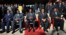 五位总统在一个阳光照映的日子里,齐聚于户外并坐在地上铺有红地毯的座位上,由左至右分别为:乌干达总统约韦里·穆塞韦尼、肯尼亚总统姆瓦伊·齐贝吉、卢旺达总统保罗·卡加梅、坦桑尼亚总统贾卡亚·基奎特与布隆迪总统皮埃尔·恩库伦齐扎。