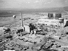 一栋大型建筑位于画面正中央,建筑旁耸立着一个高高的烟囱。两座水塔伫立在建筑旁侧。