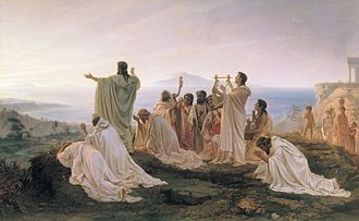Painting showing a group of people dressed in white classical garb standing at the edge of a cliff overlooking the sea watching as the sun rises. The central figure, probably Pythagoras himself, is turned away from our view towards the sunrise. He has long braids and his long beard is partially visible from the side. Both of his arms are raised into the air. The three men closest to him, two on his left and one on his right, are kneeling and making frantic gestures, possibly weeping. Behind them, an older man plays a harp and two women play lyres. A young man without a beard and an middle-aged man with a beard play lyres as well, while another young man plays the aulos. A man in the foreground at the back of the group kneels prayerfully towards the sunrise. In the background, at the far left side of the painting, a woman, a girl, a boy, and a young, naked child watch the Pythagoreans. The woman and the girl are carrying pots, indicating they have been fetching water.