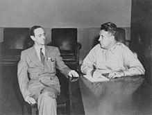 两名男子坐在桌子旁。右侧的是一个体型较大的军装男子。左侧的男子较瘦些,他穿西装、打领带,并带着眼镜。
