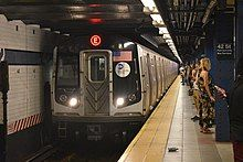 The front end of a subway train, with a red E on a LED display on the top. To the right of the train is a platform with a group of people waiting for their train.