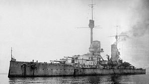 A large, light gray warship sits motionless in a calm sea