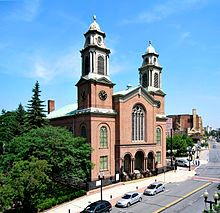 A brick church with two tall, symmetric steeples is seen in front of a city street, to the right of a wooded park.