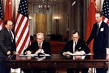 Two men in suits sit signing documents at a large table in front of their countries' flags while two others stand outside watching them.