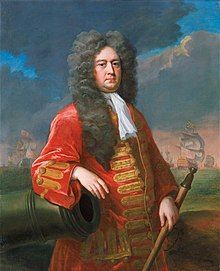 Painting of Sir George Rooke in a long flowing wig and a red coat with gold frogging, resting his right arm on a cannon and holding a rammer in his left hand. A fleet of ships is visible in the background.