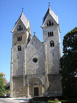 The facade of a tall grey church with paired towers and a single ornately carved doorway