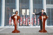 Woman and man standing in front of podiums, with flags in background