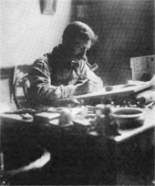 Black and white photo of man seated, drawing at a desk