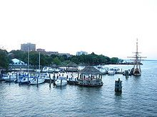 Modern photo of piers extending into quiet water with a dozen boats docked to them.