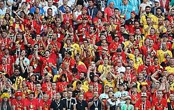 About a hundred Belgian football wearing mainly red shirts sitting in the stadium