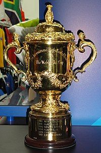 """A gold cup with two handles inscribed with """"The International Rugby Football Board"""" and """"The Web Ellis Cup"""""""