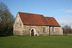 A small, simple stone church with a red tiles roof seen form an angle, with the nave in the foreground and a small chancel beyond