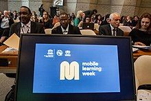 A computer screen at the front of a room of policy makers shows the Mobile Learning Week logo