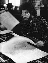 bespectacled, bushy-bearded man with dark hair, reading a music score