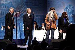 Four men standing at microphones on a stage. Three are wearing black suits. The fourth is wearing a tan jacket, dark glasses and jeans and has an extremely long white beard.