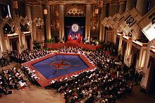 A long red table makes a pentagon around a blue floor with the NATO compass logo, while many rows of people in suits sit on all sides.