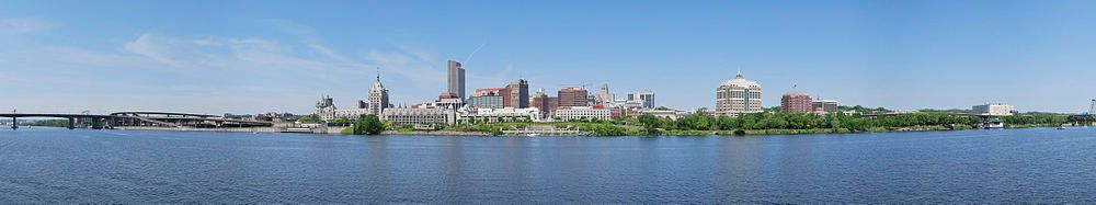 A panorama shows a river in the bottom half, crossed by a highway bridge on left; building towers are seen around the center, where a green zone on the bank of the river is seen, which extends to the right extreme of the image.