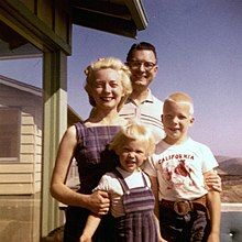 A man, woman, and two children smiling outside of a house