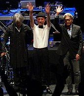 A colour photograph of three members of Yellow Magic Orchestra at the front of a stage