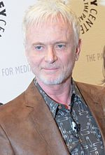 A man with blond hair, wearing a brown coat, with a great shirt.