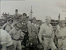 A group of men wearing military uniforms with a ship in the background