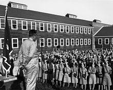 一群人站在户外,在聆听台上的人讲话。台上的人身着军装,手持军帽背在身后,面前有一架麦克风,身后是陆军工兵部队的旗帜。台下男男女女均身着军装,佩有陆军后勤兵的袖章。背景是一座两层高的楼房。