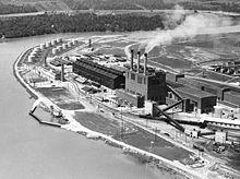 鸟瞰河畔上的工厂厂房,其中一间工厂上有三根冒烟的烟囱。