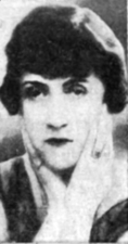 A photograph of a woman cradling her head in her hands