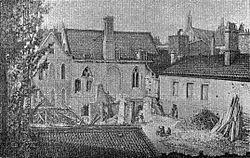 A monochrome illustration of several short buildings clustered in a small space. A yard in the foreground is filled with detritus.