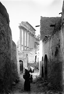 People in an alley, with ruins in the background