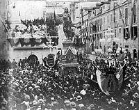 Mass of people around a statue.
