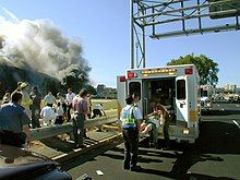 An injured victim is being loaded into a paramedic van with the burning Pentagon in the background.