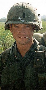 A man is at the center of the image looking at the camera. He is dressed in Vietnam-era military attire