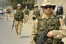A five soldiers in tan colored desert camouflage and a green camouflage vests with dark sunglasses and tan hats patrol on a street.