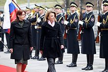 Two women in western attire walk outdoors on a red carpet along a line of soldiers in formal uniforms with rifles.