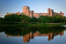 exterior of a large medieval castle with water in foreground